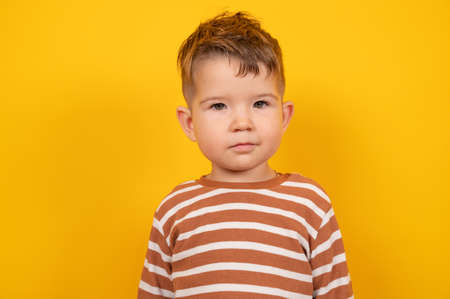 Portrait of serious cute child against yellow background. Toddler boy looking at camera. Concept of child problems and age crises. High quality photo