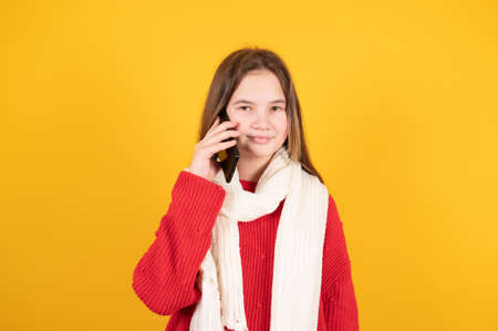 Teen girl in warm white knitted scarf talking on mobile phone isolated on yellow background. High quality photo Banque d'images