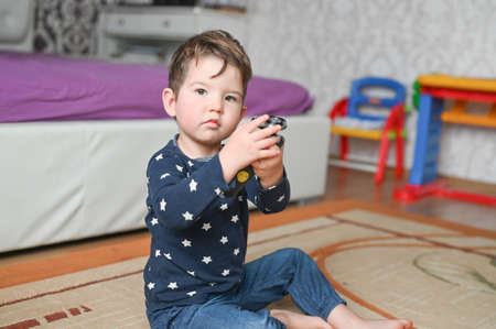 A three-year-old boy plays in the bedroom. Sleepy toddler in pajamas holding a razor. High quality photo
