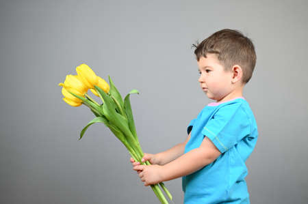 Little boy kid in blue t-shirt with a big bouquet of yellow tulips against a gray wall. High quality photo
