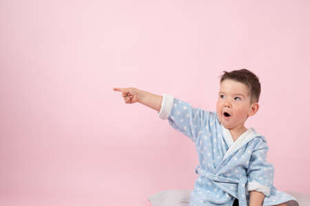 Surprised little boy points with his hand to the side, pink background with empty space. High quality photo Standard-Bild