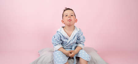 Kid boy in bathrobe sits on pillow and shows his tongue. Child boy refuses to go to bed. High quality photo