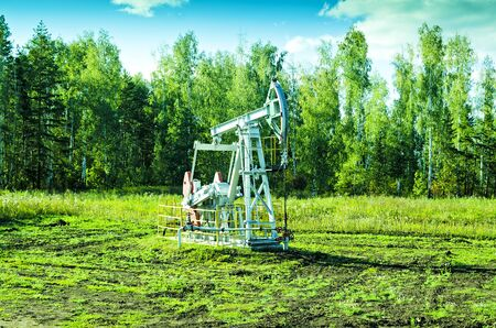 oilwell: Oil pump on chink in the field Stock Photo