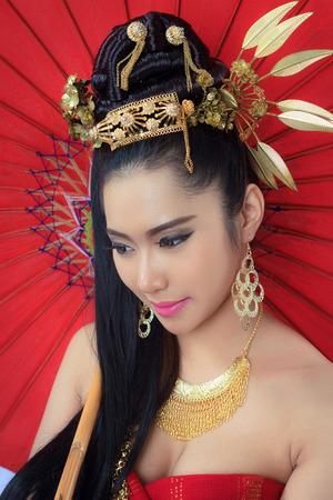 politely: Thai women with red umbrella - studio shot Stock Photo