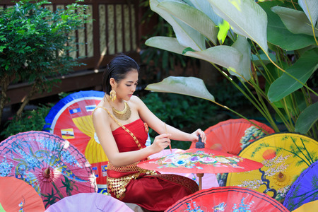 Thaise vrouw in traditionele klederdracht van Thailand schilderij paraplu Stockfoto