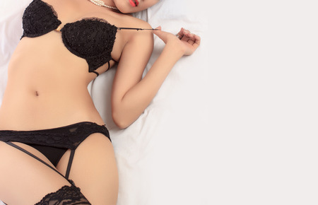 girl boobs: Young beautiful Sexy Asian woman wearing elegant lingerie posing on bed