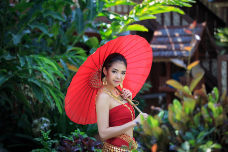 politely: Thai women in Traditional Costume  with red umbrella
