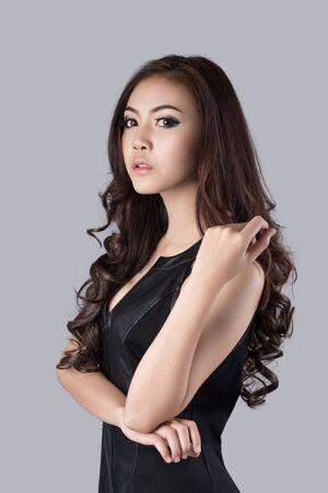 asia nude: beautiful female model wearing a leather dress - in studio Stock Photo