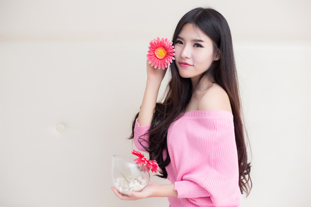 Young beautiful asian woman holding flowers