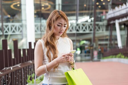 woman bag: Beautiful young woman use mobile phone and holding shopping bag Stock Photo