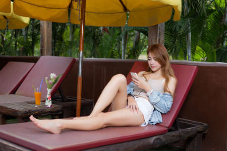 business software: Beautiful girl browsing internet in a smartphone at resort Stock Photo