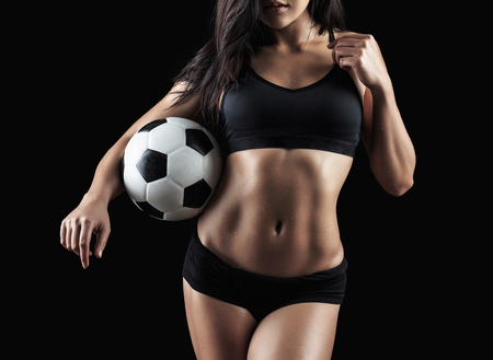 Beautiful body of fitness model holding soccer ball isolated on black background Stock Photo