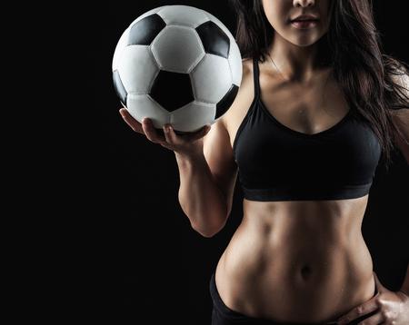 Schöne Körper von Fitness-Modell hält Fußball auf schwarzem Hintergrund isoliert Standard-Bild - 78314873