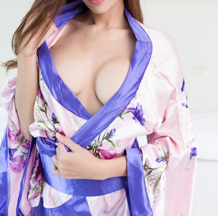 白いベッドの上の女性の美しいスリムボディ 写真素材