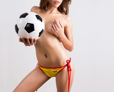 Young sexy woman with soccer ball isolated on white background
