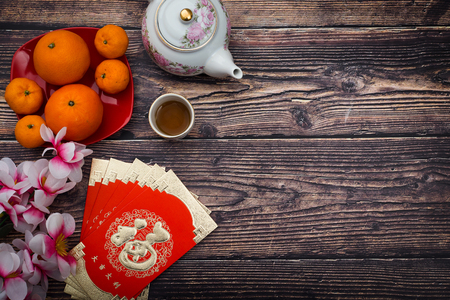 Chinese new year festival decoration with orange flower and packet in wooden background - Chinese characters mean happiness,  great luck, great profit