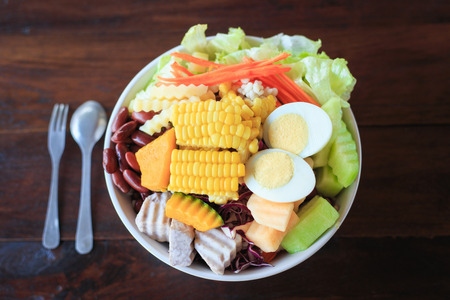 Bowl with Fresh and Healthy salad on wooden table Stock Photo
