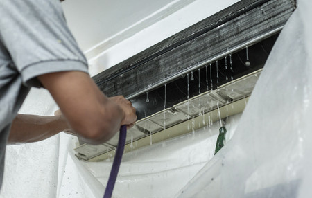 Male technician cleaning dirty air conditioner.