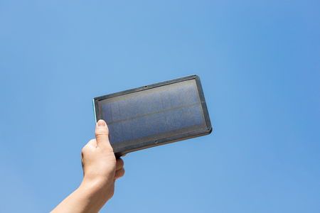 Woman hand holding Solar cell panal on blue sky background