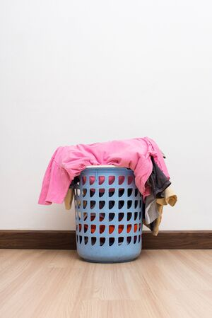 Basket with laundry on wooden floor and white wall.