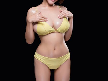 sexy young woman model in sexy bikini. Isolated on black background