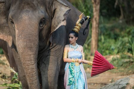 Thai girl In Traditional Costume with  elephant in Thailand