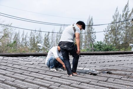 Roof repair, Male handyman repairing the roof. Foto de archivo