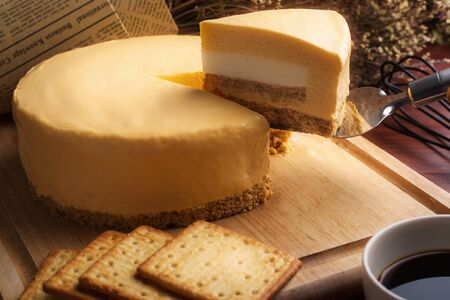 Emmental cheese cake with Mascarpone cheese cake inside with coffee and biscuit on wooden table. Homemade cheese cake.