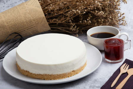 Ice box cheese cake with strawberry jam and a cup of coffee on the table. Homemade cheese cake. Foto de archivo