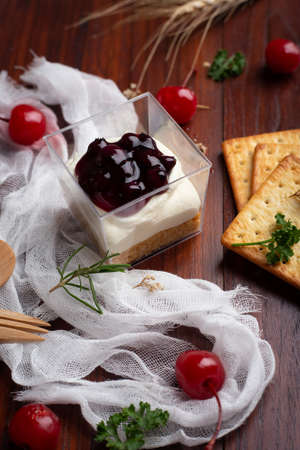 Blueberry cheese pie with cherry and Biscuits on wooden table. Homemade Bakery concept. Foto de archivo