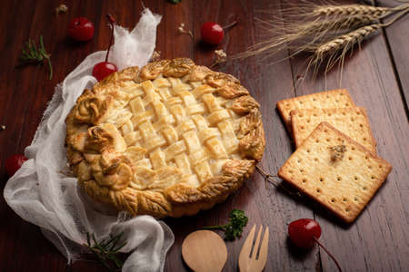 Apple pie  with red cherry on wooden table. Homemade Bakery concept. Foto de archivo