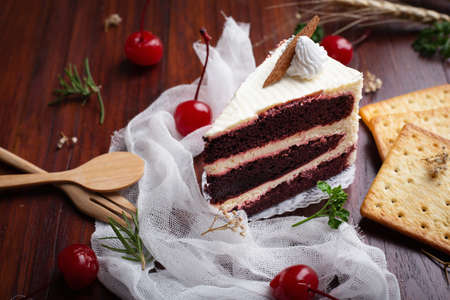 Red velvet cheese cake with cherry and Biscuits on wooden table. Homemade Bakery concept.