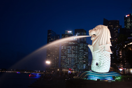 Merlion on twilight with high tower background, landscape, Singapore Editorial