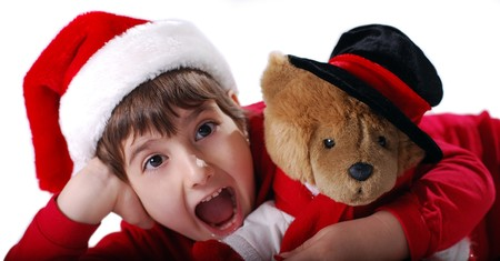 Excited Christmas Kid with hat and teddy bear photo
