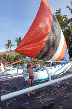 BALI ISLAND, INDONESIA - AUGUST 29,2012: A man ties a sail to a boat on the beach