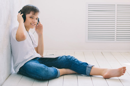 listens: A young man sits on the floor and listens to music in the Studio. Stock Photo
