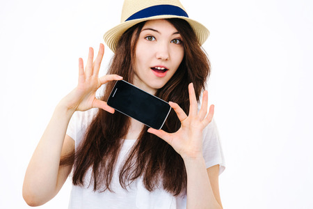 mobile phone screen: Beautiful girl holding a phone on white background in Studio.