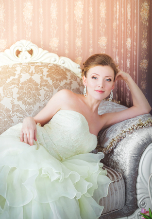 luxurious sofa: Beautiful young bride lying on a luxurious sofa.