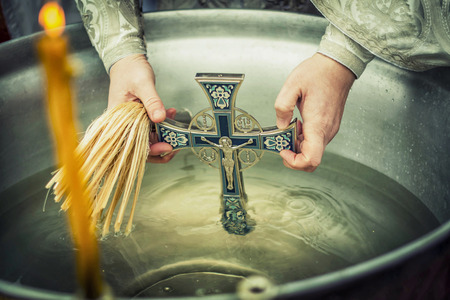 baptize: A Christian holiday Epiphany, a Cross immersed in the Holy water Stock Photo