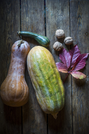 pumpkin, zucchini, nuts, and autumn leaf on wooden background of aged wood