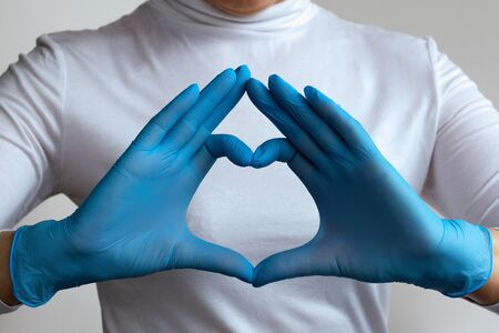 Woman doctor's hands in blue gloves form a heart shape in home. stay home. Close-up. hands in blue medical latex gloves. Hand gestures for expressing emotions. Medical healthcare. Stock Photo