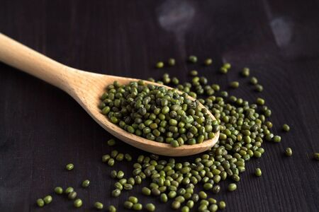Close-up mung beans in a wooden spoon. green mung beans in spoon on a black