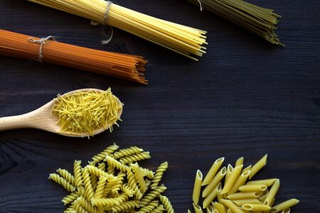 raw spaghetti and pasta on a wooden table with copy space. top view. uncooked Spinach spashetti, wheat pasta and tomato spaghetti with fusilli, penne on a black background. Italian Cuisine Banque d'images