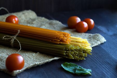 raw pasta and fresh vegetables, cherry tomatos on a wooden table with sackcloth. uncooked wheat, Tomato and Spinach spaghetti and ingredients on a dark background. Italian Cuisine Banque d'images