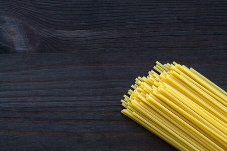spaghetti pasta background. wheat spaghetti on wooden table. raw pasta on black background with copy space. top view. Italian Cuisine.