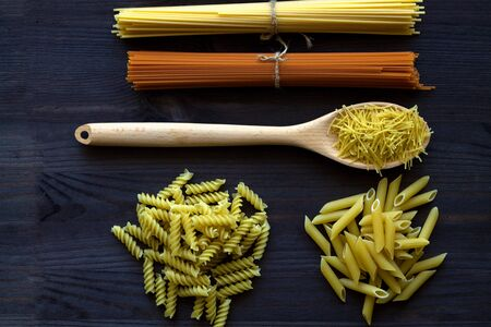 Different types of raw pasta on a wooden table. uncooked wheat and tomato spaghetti, fusilli, penne on a dark table. top view. Italian Cuisine Banque d'images