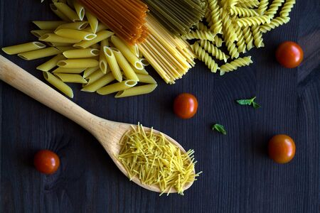 pasta and vegetables. different types of Italian pasta on a wooden table with copy space. raw Spinach spashetti, wheat pasta and tomato spaghetti with fusilli, penne with cherry tomatoes on a black. top view.