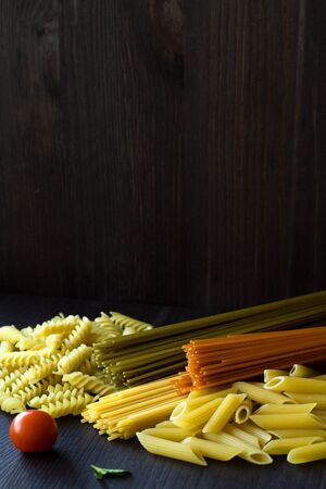 different types of pasta on a wooden table with copy space. uncooked Spinach spashetti, wheat pasta and tomato spaghetti with fusilli, penne on a black background. Italian Cuisine. vertical