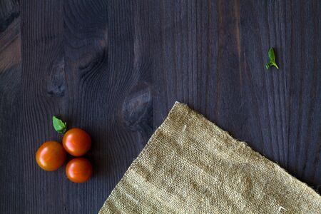 red cherry tomatoes and green leaves with sackcloth on a wooden table with copy space. top view. Banque d'images