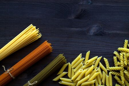 raw spaghetti and pasta on a wooden table with copy space. top view. uncooked wheat, Tomato and Spinach spaghetti and fusilli, penne on a dark background. Italian Cuisine